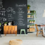 Dining room with chalkboard wall wooden chest and kitchen cart